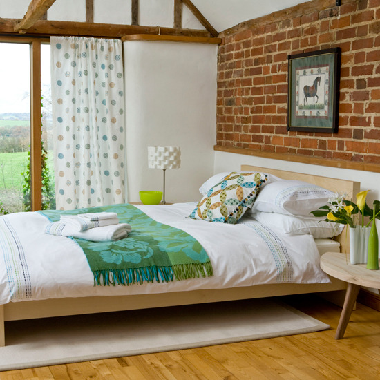 Country bedroom with brick wall
