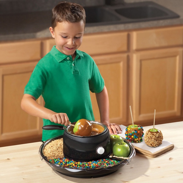 A kid using the Home caramel apple maker