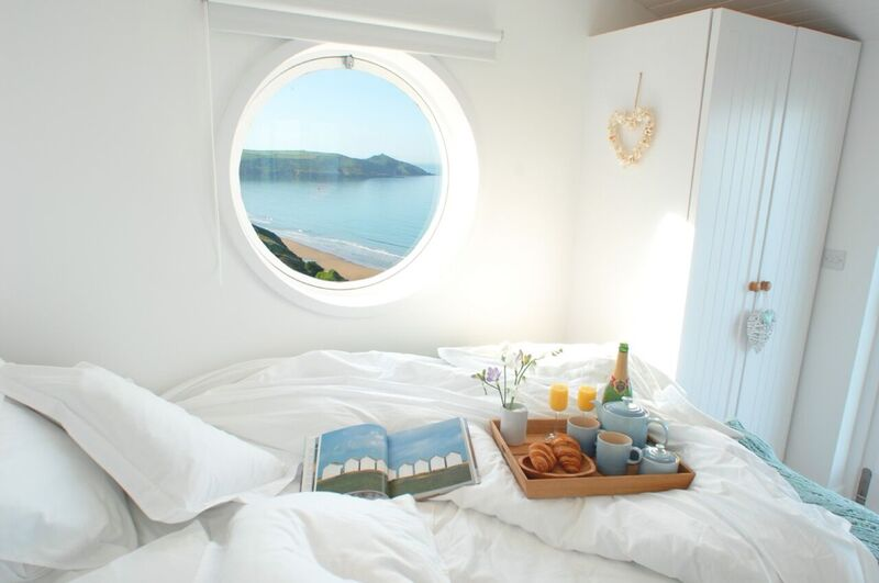 Small white bedroom with round window