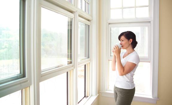 Woman having tea by the window