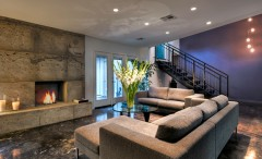 Stylish basement living room desidn with concerete fireplace
