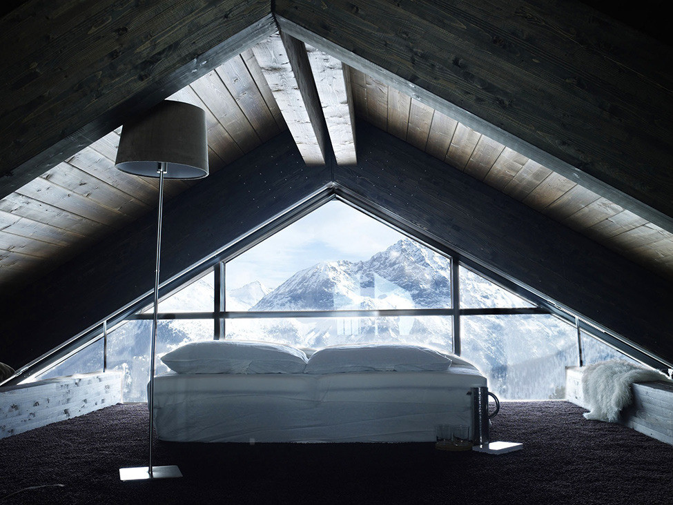 Attic bedroom with glass wall and mountain view