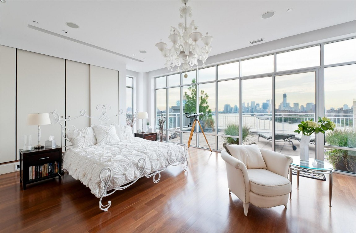 White bedroom with floor-to-ceiling windows and city view