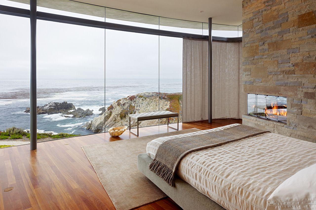 Bedroom with floor-to-ceiling glass wall and ocean view