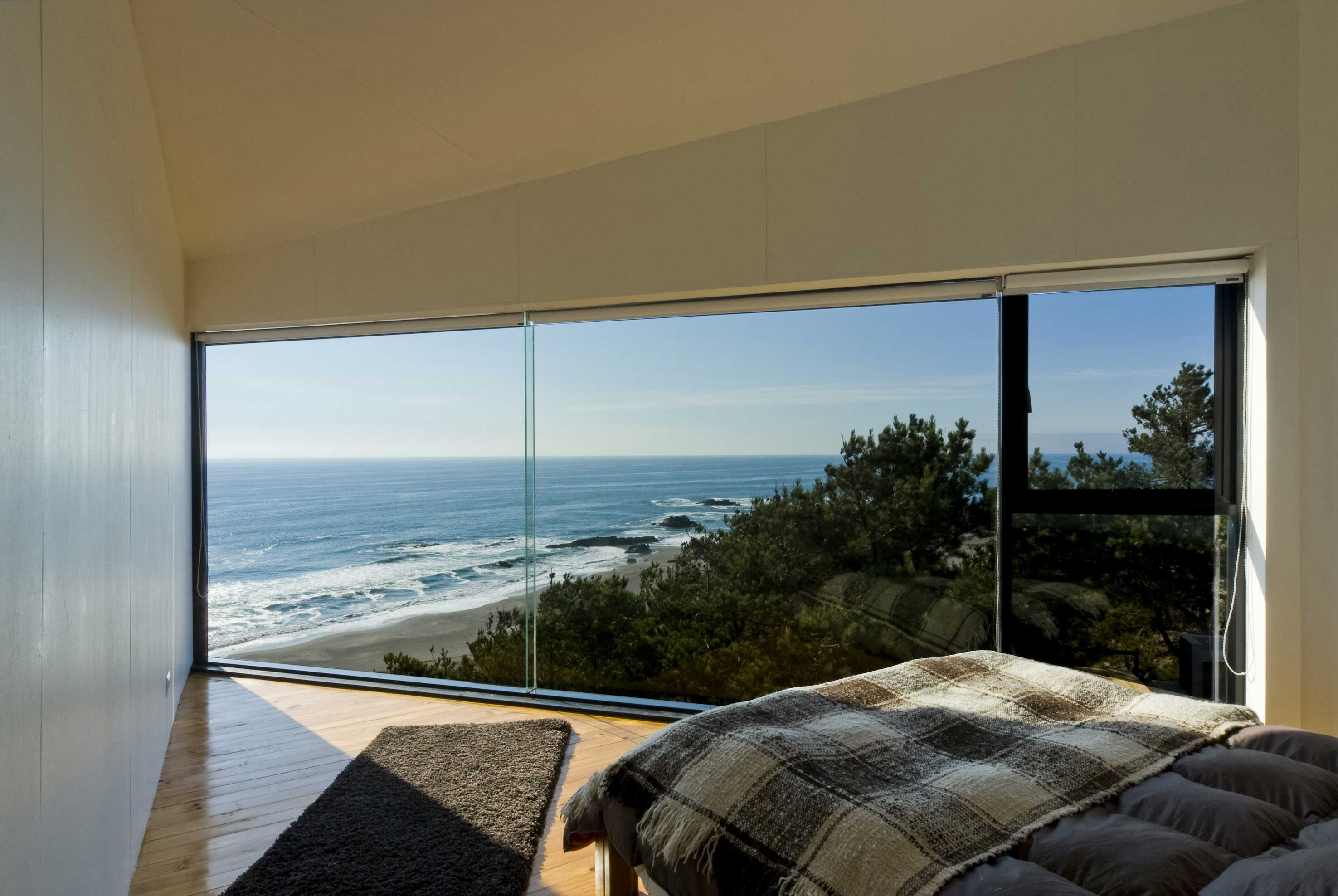 Angular bedroom with a floor to ceiling glass wall and ocean view. The Greatest Selection of Bedrooms With Floor to Ceiling Windows