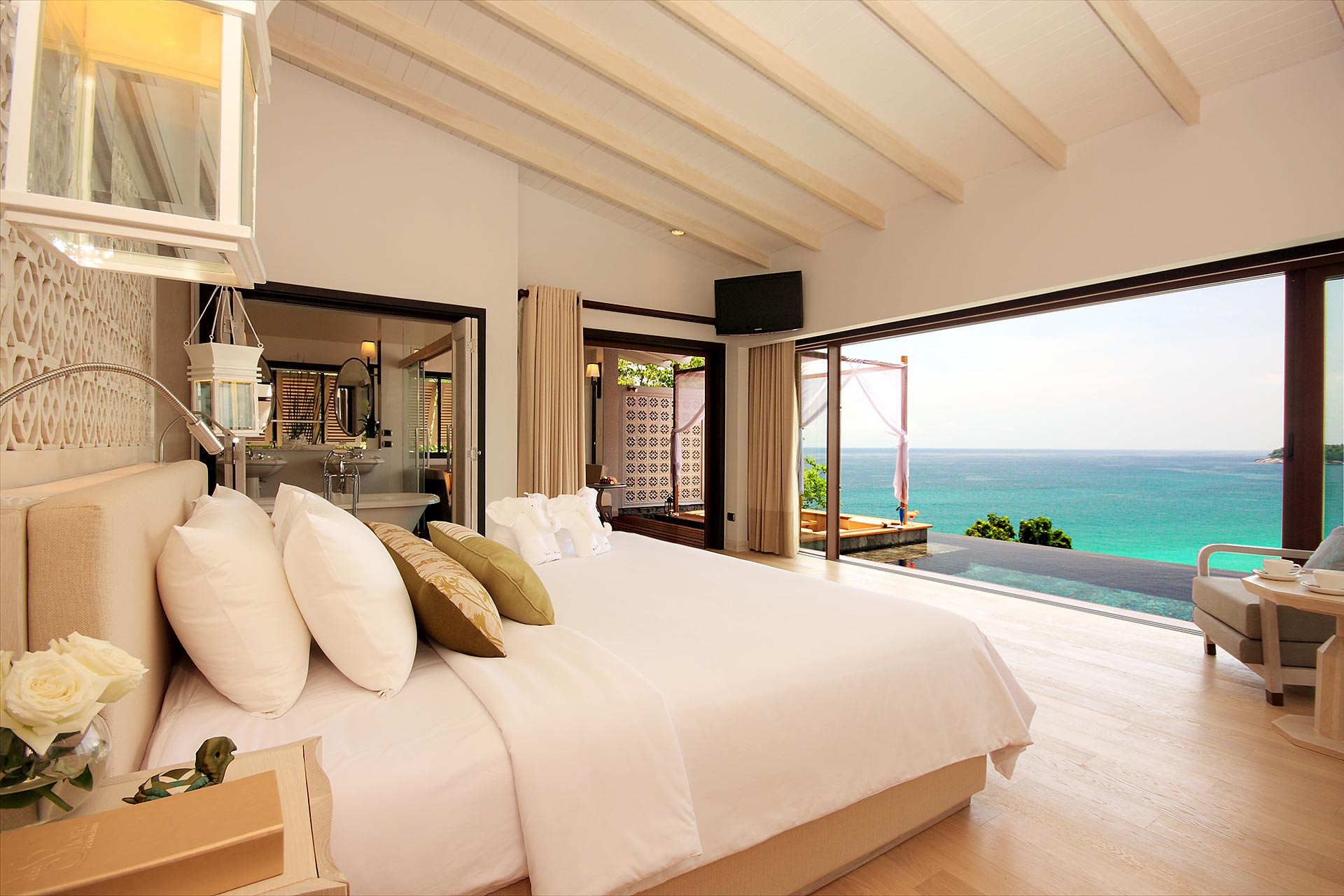 Hotel room with floor-to-ceiling windows and ocean view