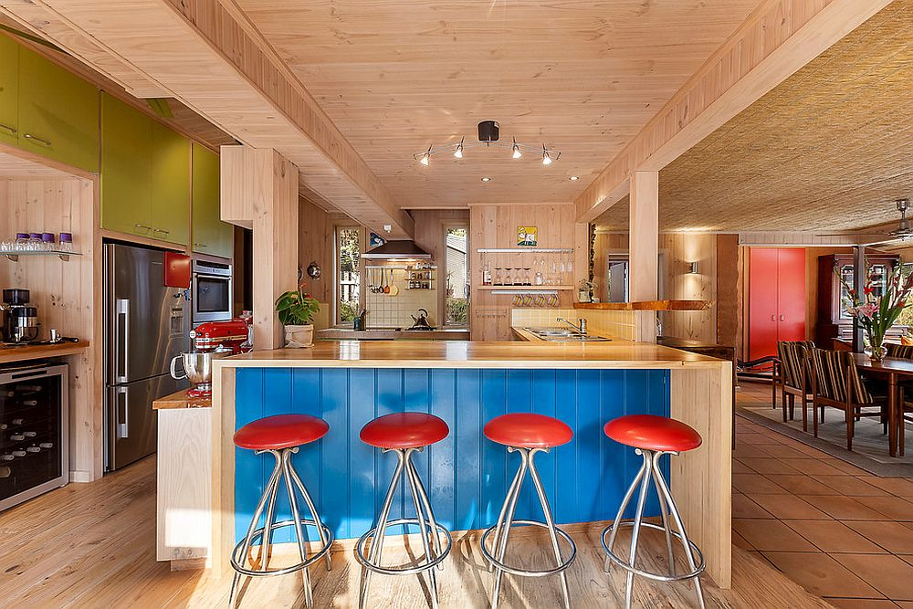 Blue kitchen island with red chairs