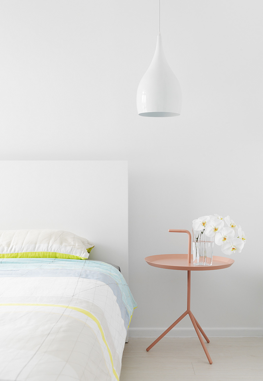 White bedroom with a pastel nightstand