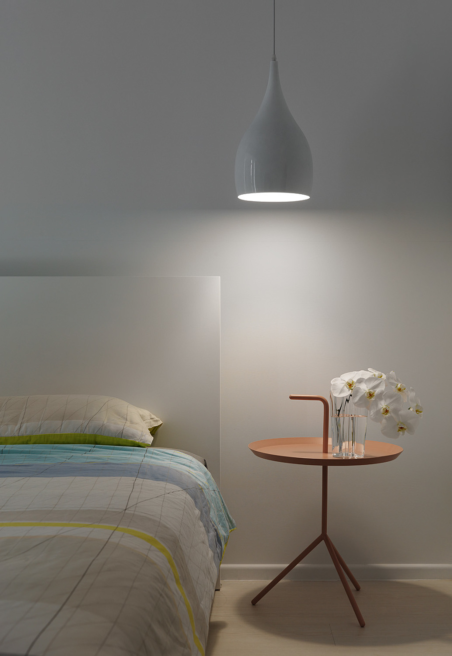 White bedroom with a pastel nightstand by night