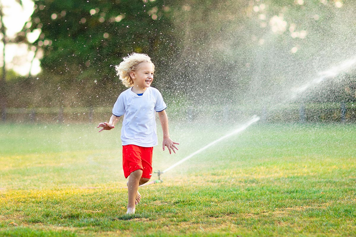 Child playing with sprinklers