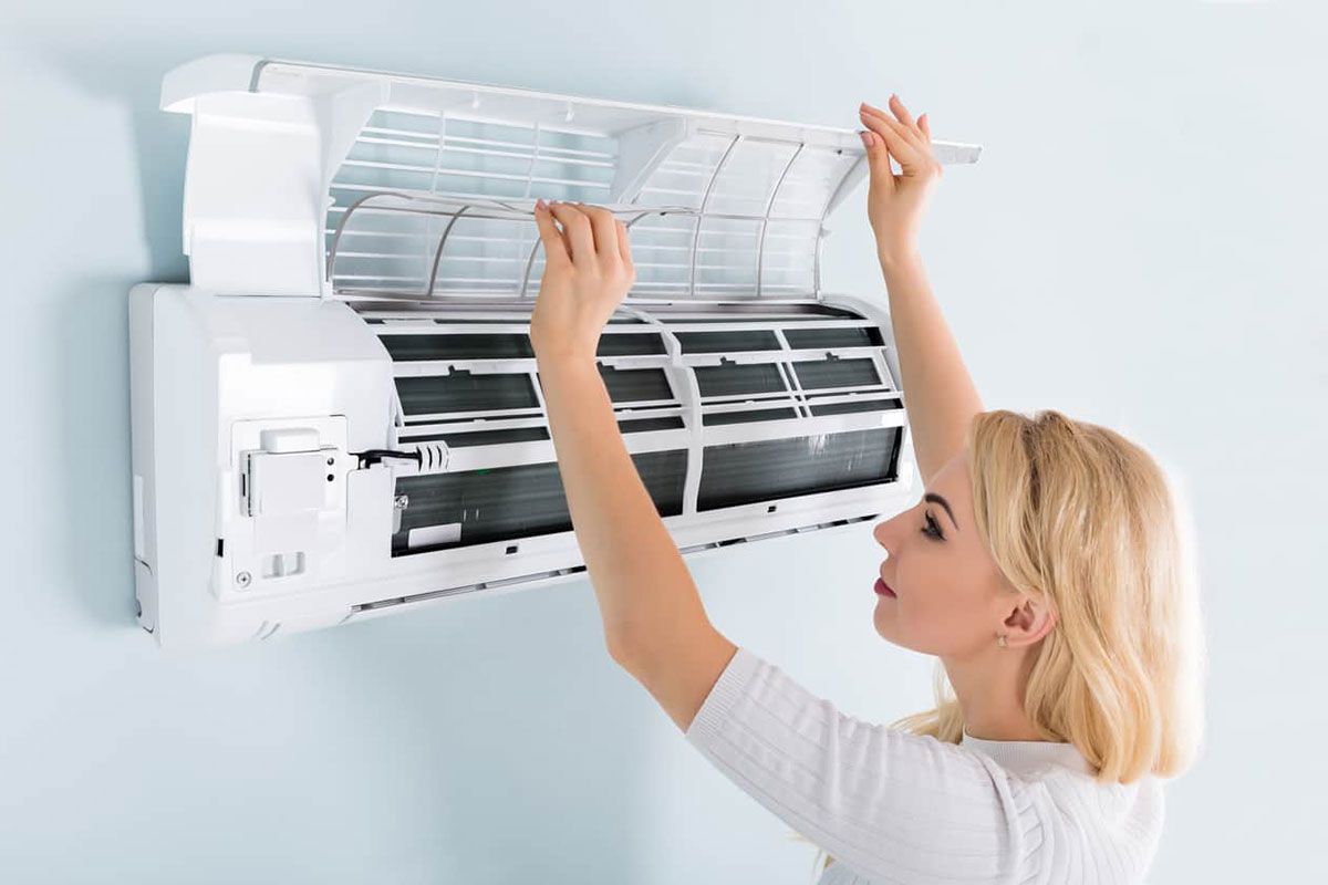 Woman cleaning AC filters